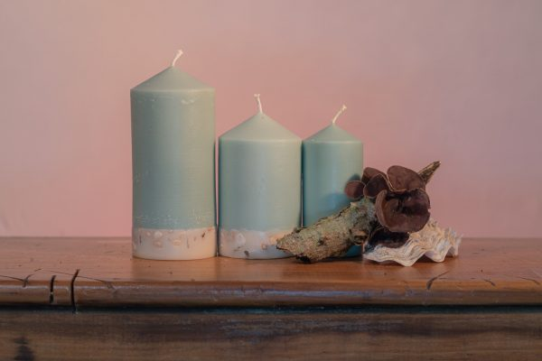 Essential oils of Himalayan Patchouli and Sandalwood create a sophisticated scent reminiscent of the swinging 60s' counter-culture. Teal coloured, this elegant candle features a crisp white base embedded with river pebbles.
